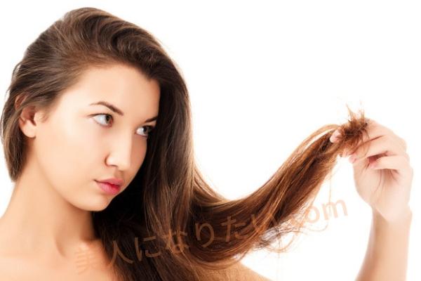 枝毛を見つめる女性